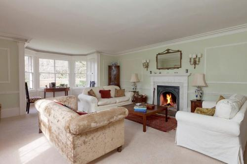 Gracious sitting room with open fire, antique furniture and 3 sofas