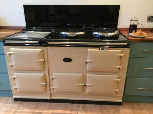 4 door cream Aga with black marble splash back